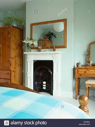 simple wooden framed mirror above fireplace in townhouse bedroom