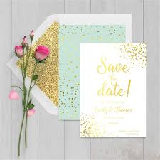 gold foil and mint save the date cards with glitter lined envelopes