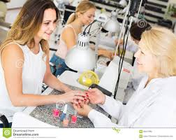 female clients doing nails in nail salon in afternoon stock photo
