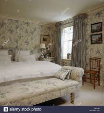 blue white floral chaise longue and matching wallpaper in bedroom