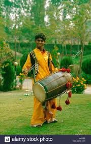 a teenage indian boy wearing traditional costume stands in a
