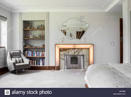 light grey armchair and bookshelves beside art deco fireplace and light grey armchair and bookshelves beside art deco fireplace and mirror in 1930s london bedroom