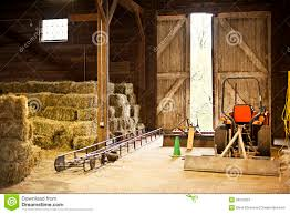 barn interior with hay bales and farm equipment stock image