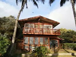 two story red beach house with tall coconut trees on oahu hawaii