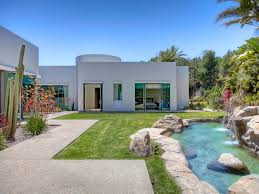 a modernist beverly hills compound designed by richard landry the landscaped property includes multiple outdoor dining areas and water features and is planted with roses lilacs and lavender as well as mature palm