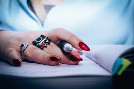 person with red nail polish holding black pen free stock photo