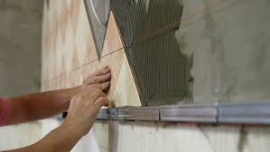Kitchen Wall Ceramic Tile - man u0027s hands installing ceramic tile to a kitchen wall close up