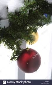 ornaments hanging from a garland on a porch railing with