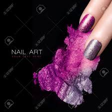 fingers with silver purple nails and crushed eye shadow with