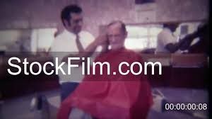 1963 old man getting trim haircut in barber shop chair des