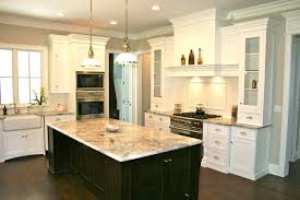 white kitchen cabinets with black island the white cabinets island wood floors
