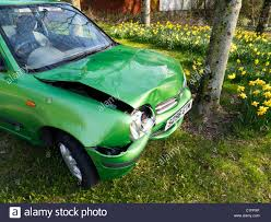 small green nissan micra car after frontal crash into tree on