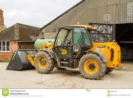 construction digger loader in farm yard with barn editorial