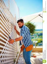 young man decorating the house wall by setting up the