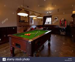 the pool table in the games room of an old english pub or public