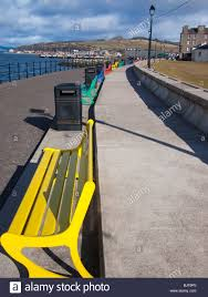 brightly painted benches at the seafront in largs scotland stock