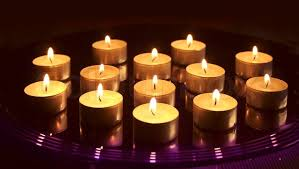 small candles burning on glass tray on background