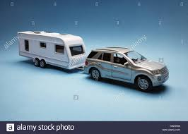 car toy blue toy car towing a caravan of generic design on blue background