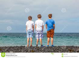 three teen boys stand at a black volcanic beach stock photo