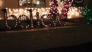 merry sign hung from a tree lights