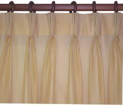 interior beige pinch pleat drapes with brass holder also hanging