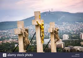jesus christ cross on calvary with suburb and hill in background
