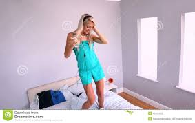 attractive blonde dancing on bed and listening to music stock