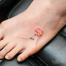 small pink flower tattoo on foot by graffittoo
