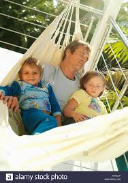 father and children 5 8 relaxing in hammock on balcony smiling man