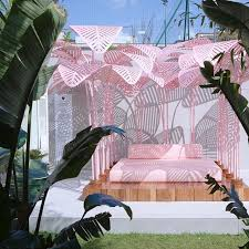 outdoor palm tree l relax on a cushiony bed under pink palm tree leaves le refuge