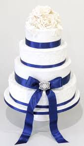 white and blue ribbon white sugar flowers on this 4 tier wedding cake with royal blue