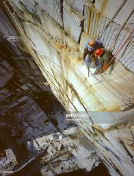 narrow picture ledge stonecutter riggers with pneumatic drill on ledge of granite quarry