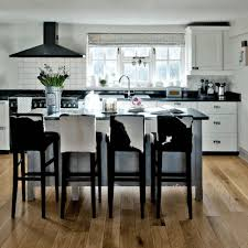 white kitchen cabinets with black island orange dining chair huge white chircle hanging light single bulb