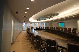 round glass conference tables and brown leather swivel chairs and