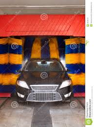 black car in automatic car wash rotating blue and yellow brushe