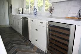 Herringbone Tile Floor Kitchen - contemporary galley kitchen features creamy white cabinets paired