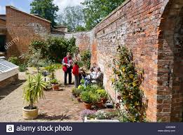 visitors in the old walled garden at rowdeford house wiltshire uk