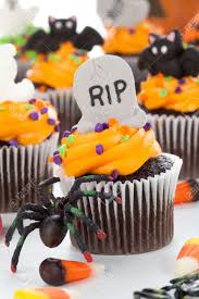 halloween cupcake with rip ghost and bat decorations surrounded