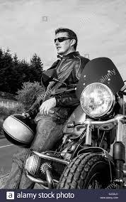 white motorbike jacket man motorbiker leaning on motorbike holding helmet leather jacket