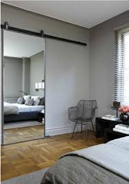 mirrored doors over part of storage behind bed head wall