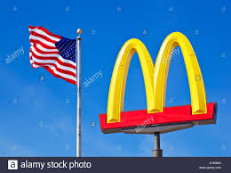 A American Flag Pictures Mcdonald U0027s Logo Arches Sign Against A Clear Blue Sky With An