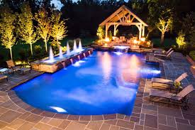 craftsman swimming pool with exterior travertine tile floors