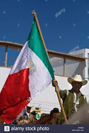 mexican cowboys ride with a mexican flag at the festival of the