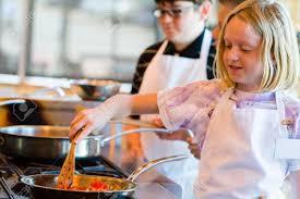 cour de cuisine enfant enfants apprenant à cuisiner dans un cours de cuisine banque d