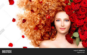 beauty model with long curly red hair and beautiful red roses
