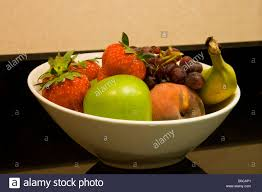 close up of white fruit bowl with apple strawberries peach banana