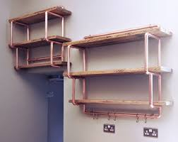 a wall mounted shelving unit made from copper pipe and reclaimed
