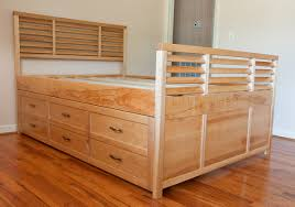 custom queen size bed with tiered drawers underneath and shutter