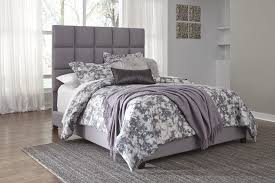 gray upholstered bed with square pattern headboard top drawer