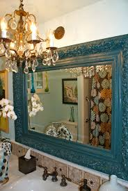 blue wooden frame of bathroom mirror chandelier white wall paint